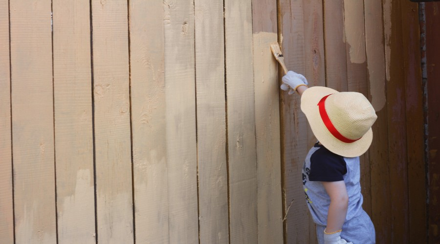 A child painting a fence wearing a straw sun hat