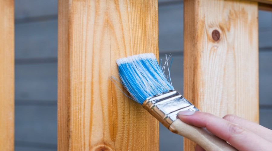 A person staining a wooden fence with a paintbrushy