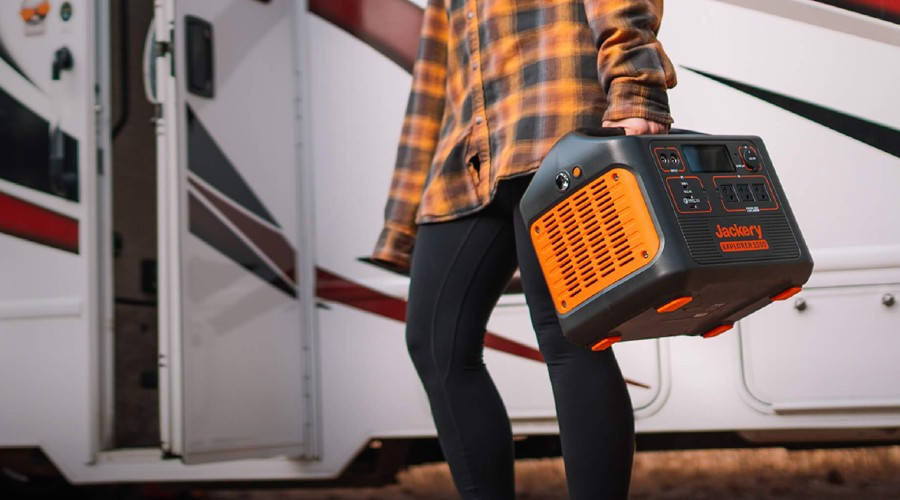 a person wearing a plaid shirt and carrying a Jackery portable power station outside an RV