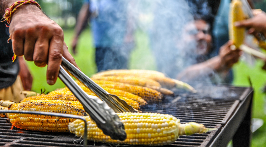 guy cooking corn directly on grates