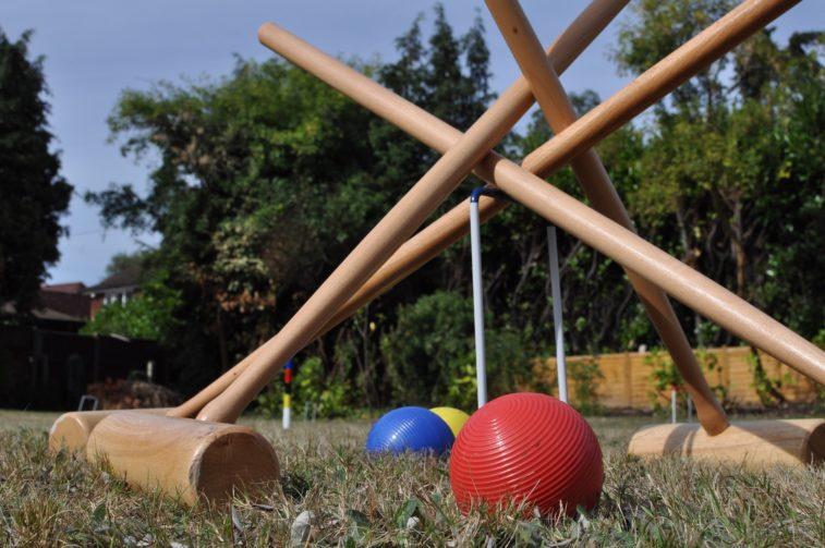 Croquet mallets standing above the balls