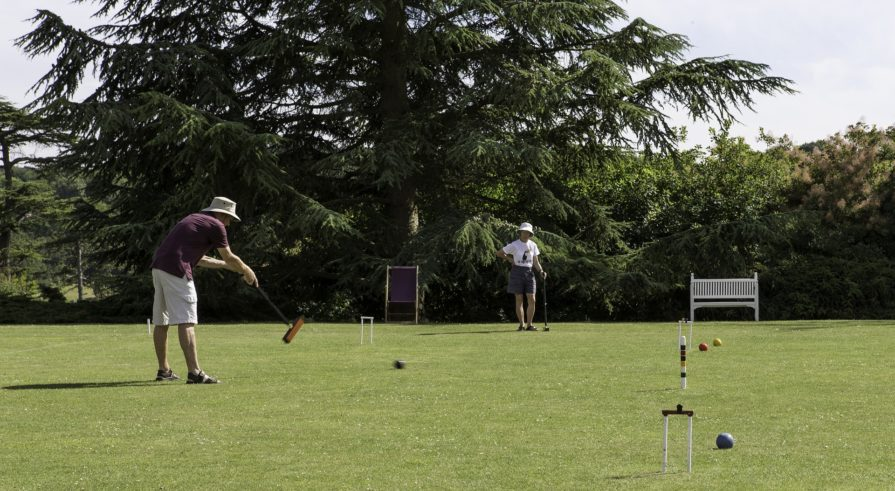 Two people playing Croquet during a sunny day