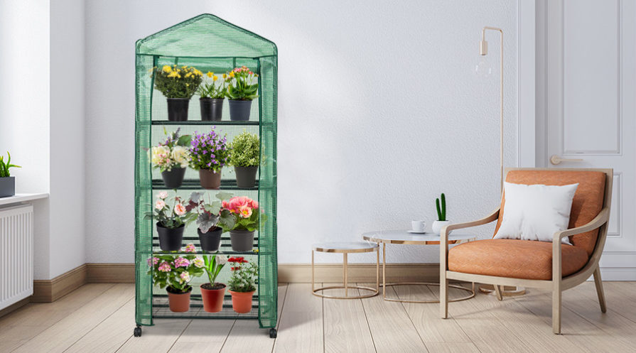 greenhouse filled with plants in living room with chair beside it