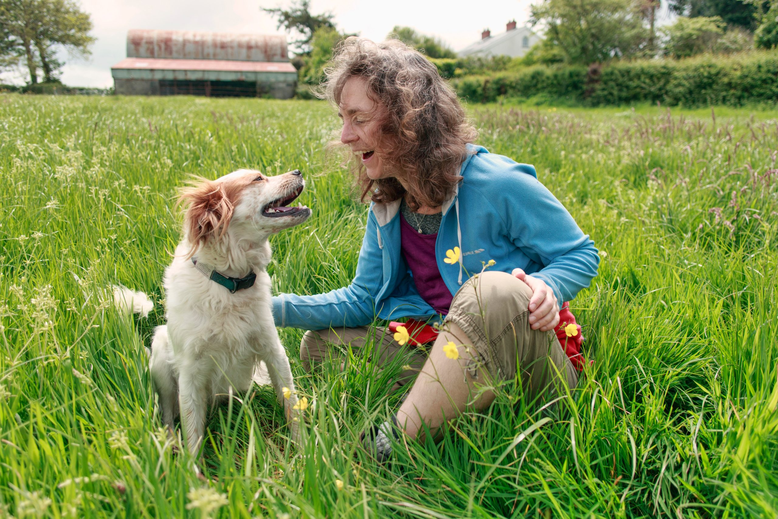 woman sitting with her dog in the grass