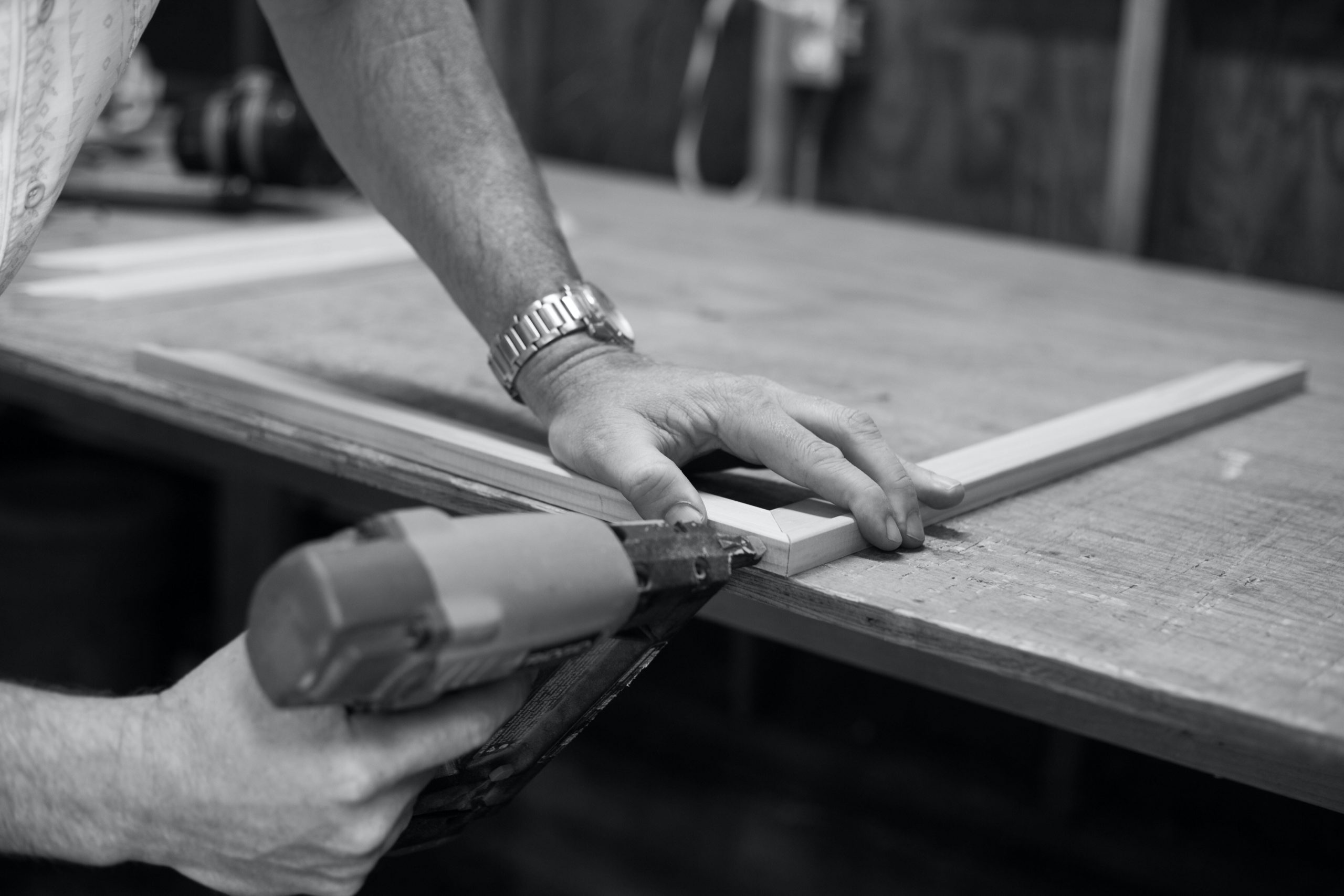 Man wearing a watch and using a nail framer