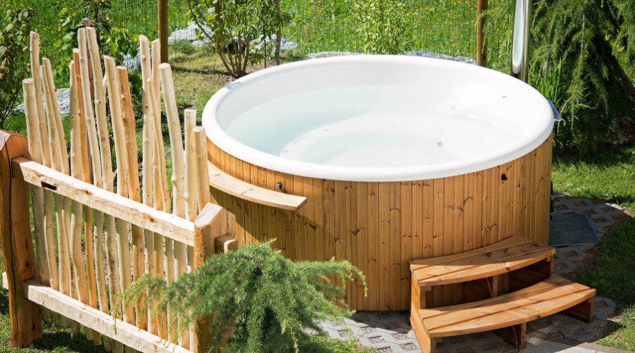 Wooden hot tub with greenery in background and rustic privacy fence