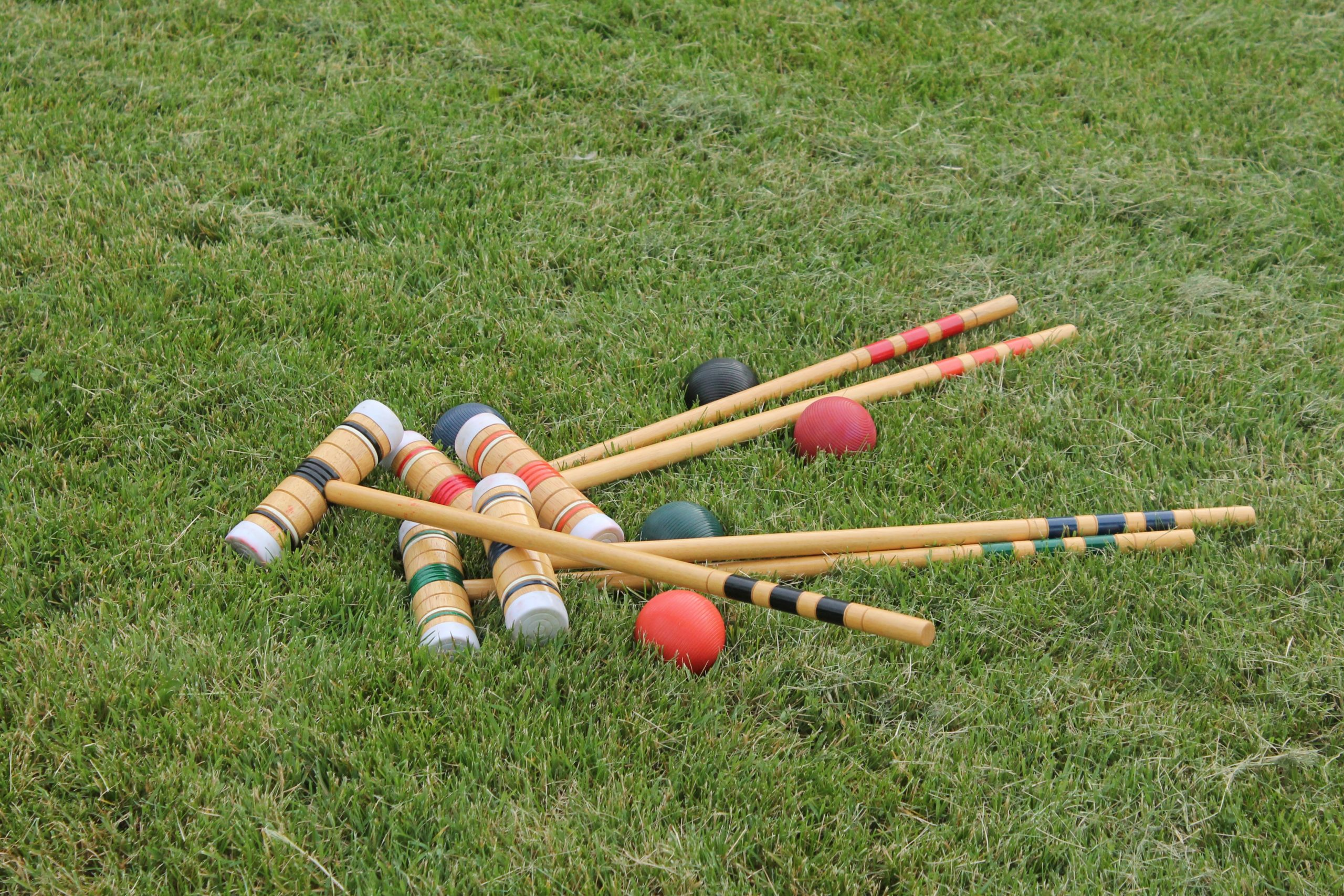 Croquet mallets and balls lying on the grass
