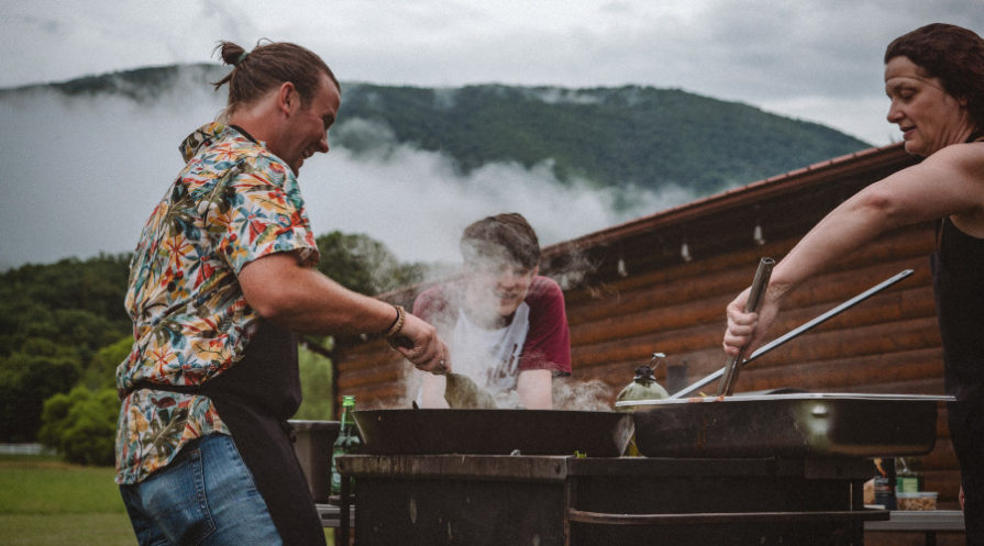 Three adults cooking around an outdoor BBQ with mountains in the background