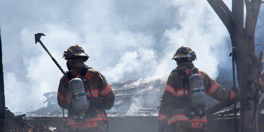 Firemen Using Axe To Clear Debris