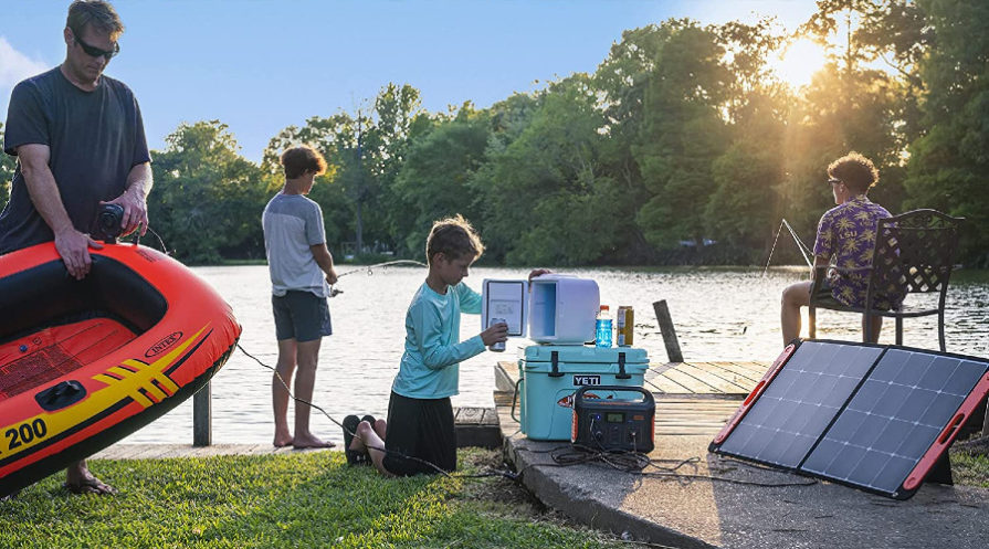 Family camping by lake with small solar generator and solar panels set up
