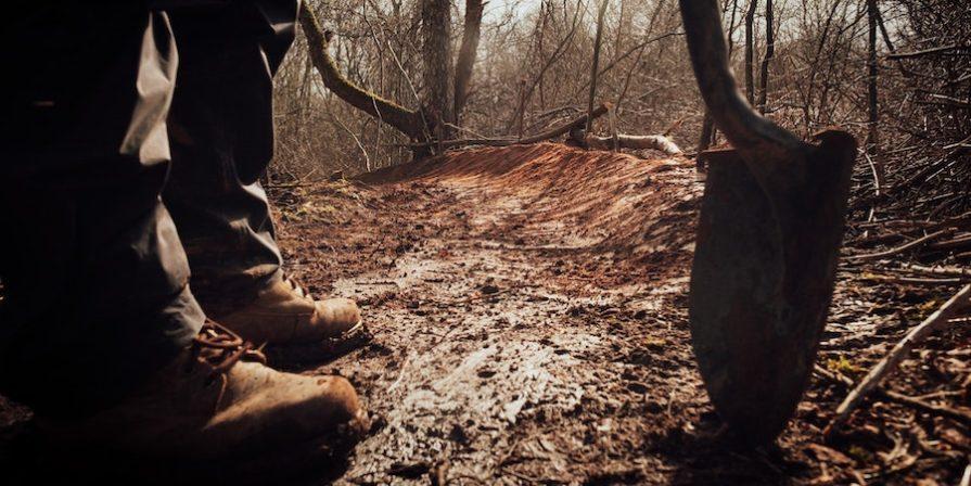 Legs And Shovel On Muddy Path