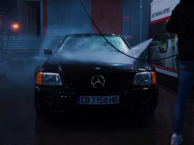 A man washing his car using a pressure washer