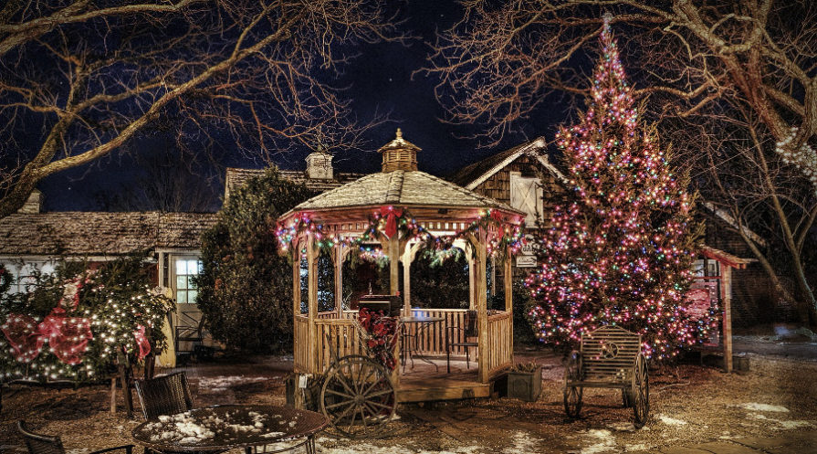gazebo, fence, and other wooden structures lit up with Christmas lights