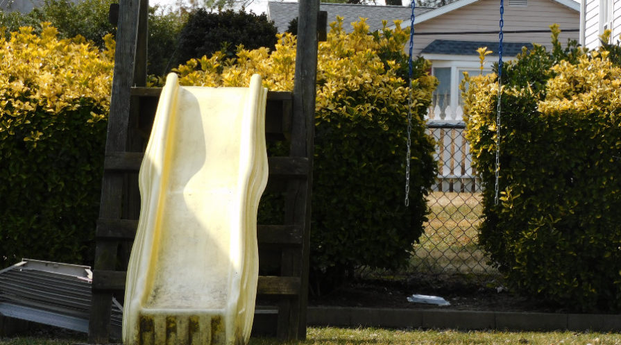 slide and swing set in backyard
