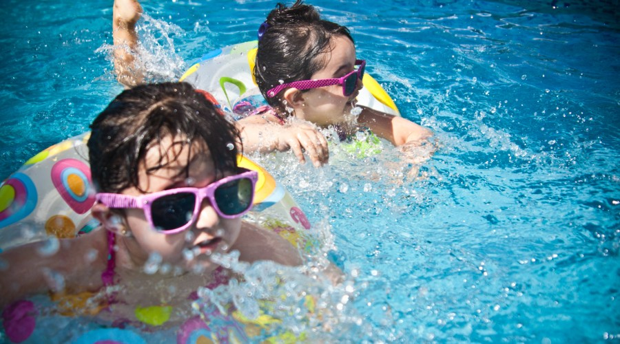 two children wearing sunglasses and bathing suits in the pool with ring floats
