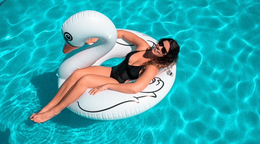 a woman wearing a black bathing suit floating in a pool on a swan inflatable