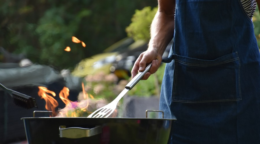 A person holding a grilling spatula over a grill with flames