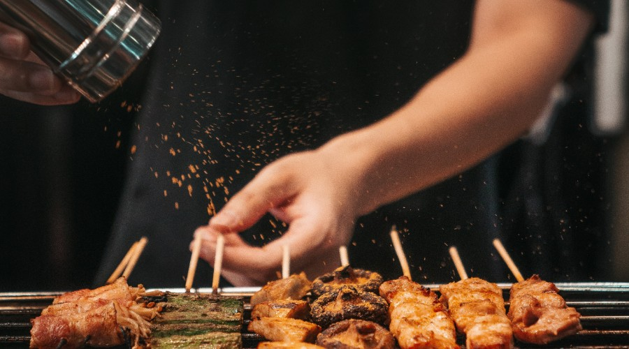 A person shaking spices on shishkabobs on the grill