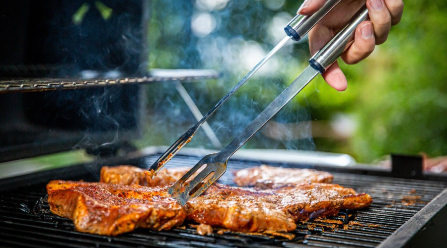 A person's hand reaching out to flip steak on a bbq