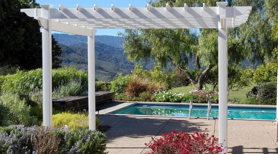 A white pergola set up next to an inground pool