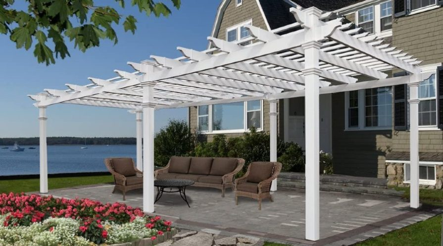 A white pergola on a brick deck area with a couch and chairs beneath it