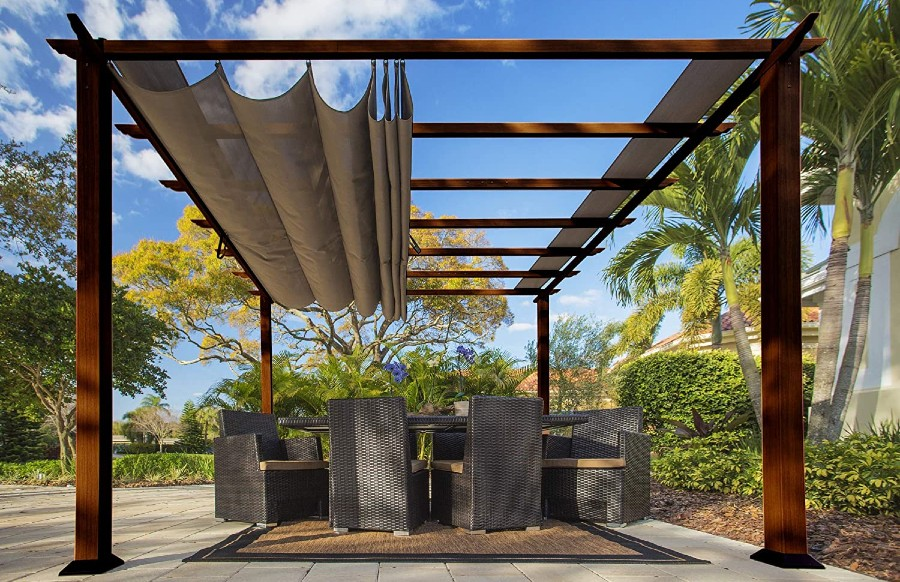 A pergola with a canopy set up with a table and wicker chairs beneath it