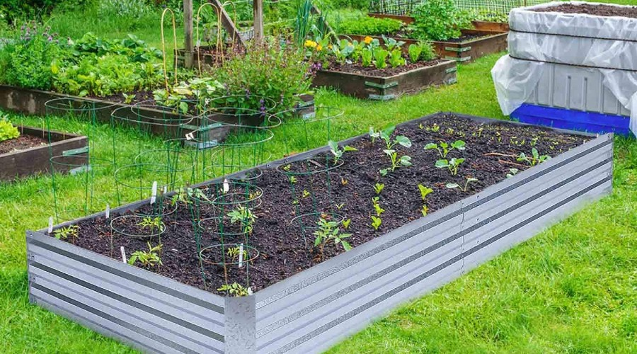 a metal raised garden bed installed in a grassy area and fully planted