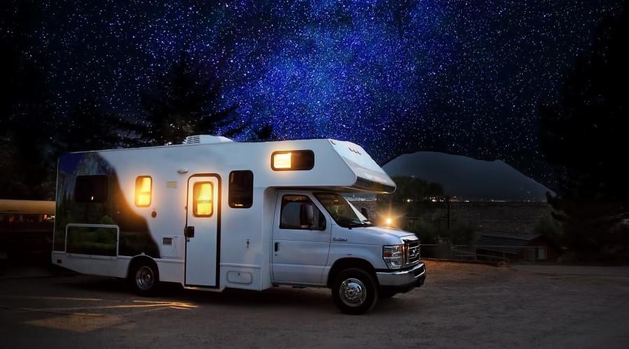 RV camper at night, Milky Way visible behind, lights inside