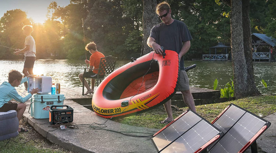 family gathered on dock, man holding inflatable raft, children by water, solar generator and panels set up