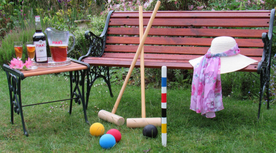 croquet set leaning against garden bench with tea on table and jacket draped on bench
