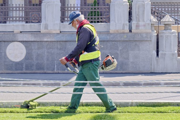The man mowing the lawn with a weed eater