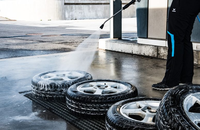 A man washing tyres with a pressure washer