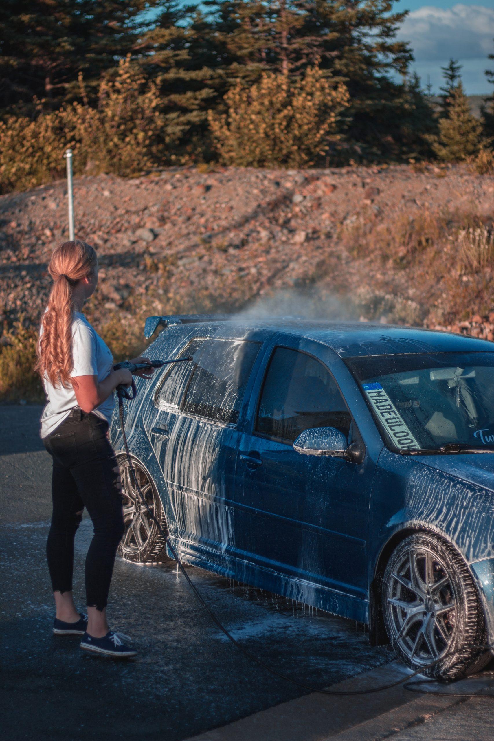 woman power washing car