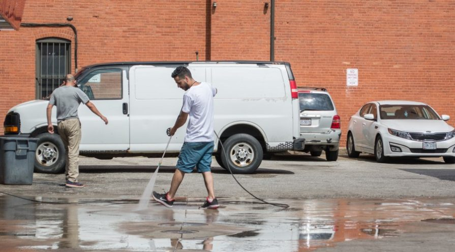 A man wearing a white tshirt and blue shorts power washing a parking lot space