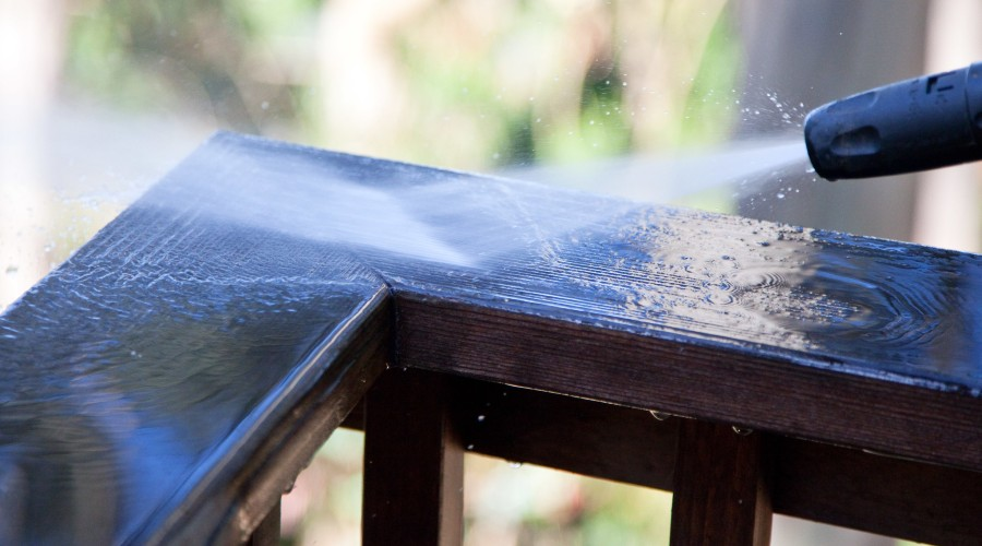 A pressure washer being used to clean the top railing of a deck