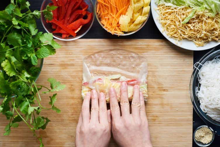 A person rolling a spring roll with vegetables