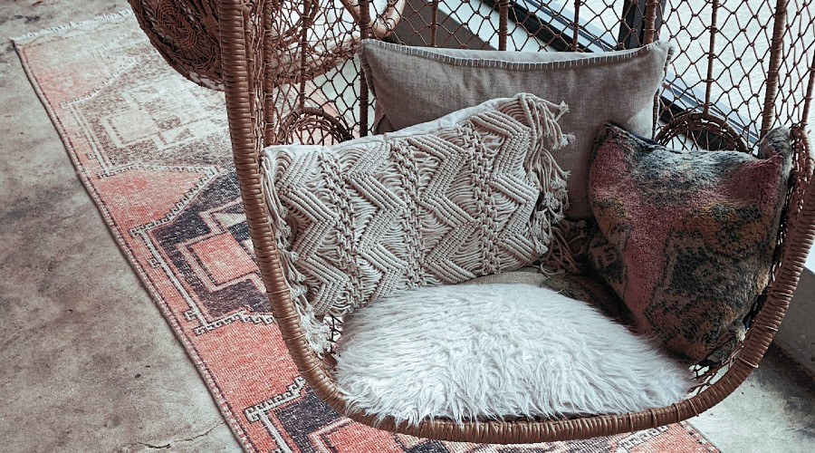 four different grey pillows sitting in a hanging wicker chair