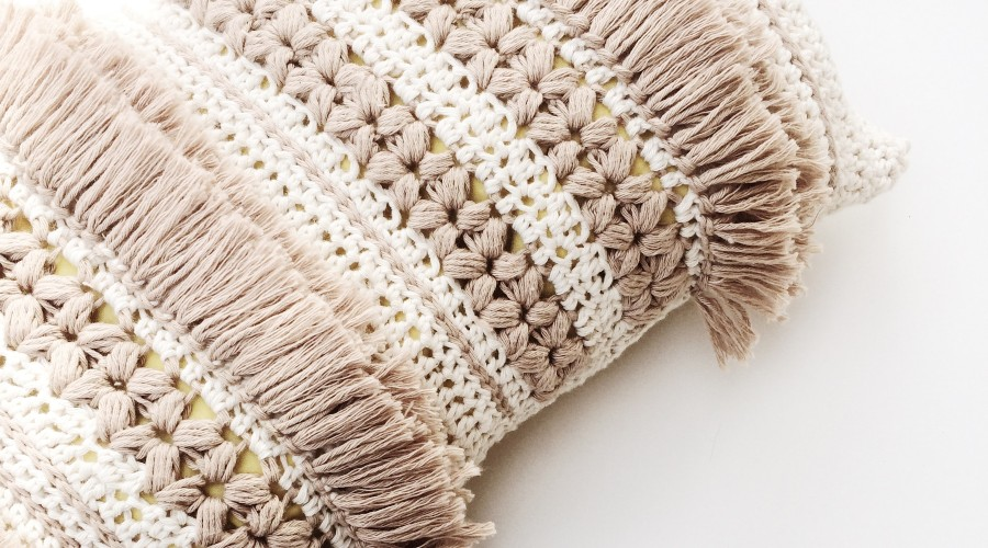 Close view of a white and beige crocheted pillow
