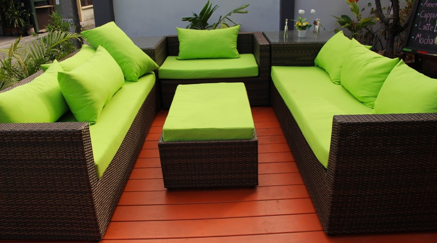 Two dark wicker couches and a chair with matching lime green cushions and throw pillows