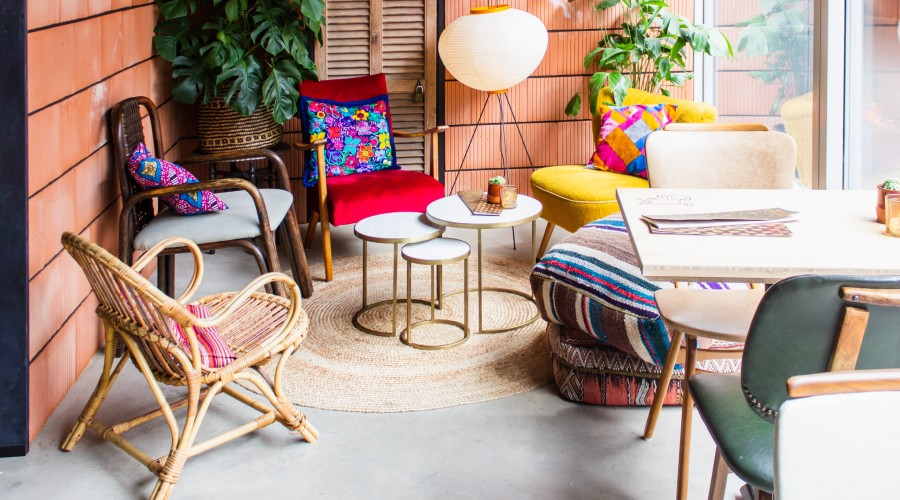 a small outdoor seating area with chairs and throw pillows of different colors and styles