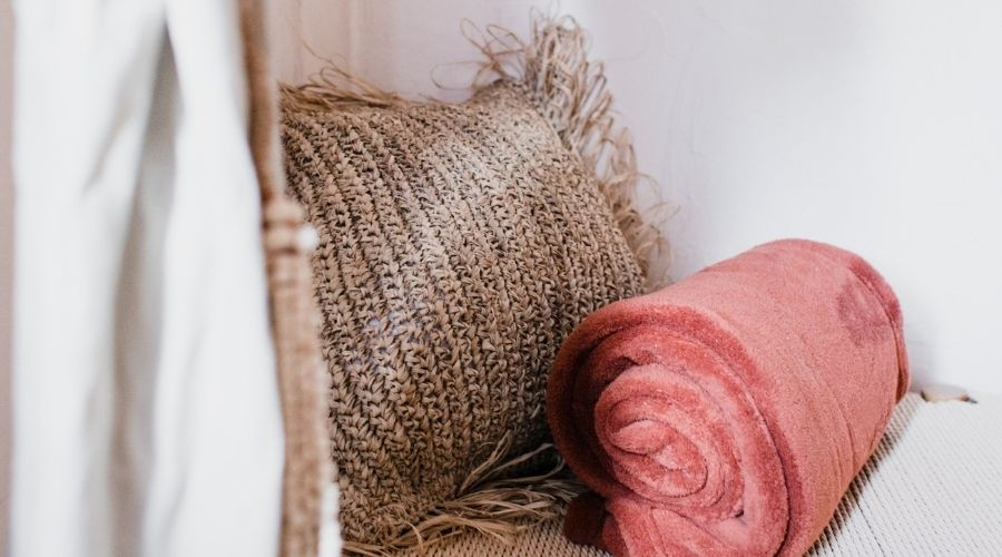 A brown throw pillow next to a coral rolled up blanket