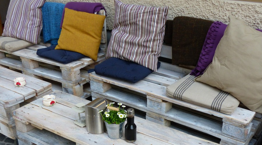 an assortment of different colored throw pillows on a bench made from pallets