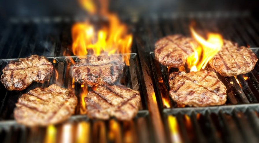 meat over open flame of grill