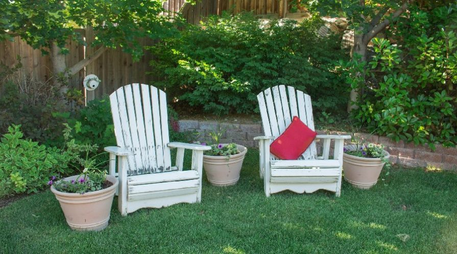 Two Adirondack chairs in a garden