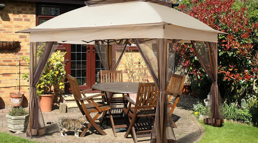 dining table and chairs sitting under a backyard canopy tent