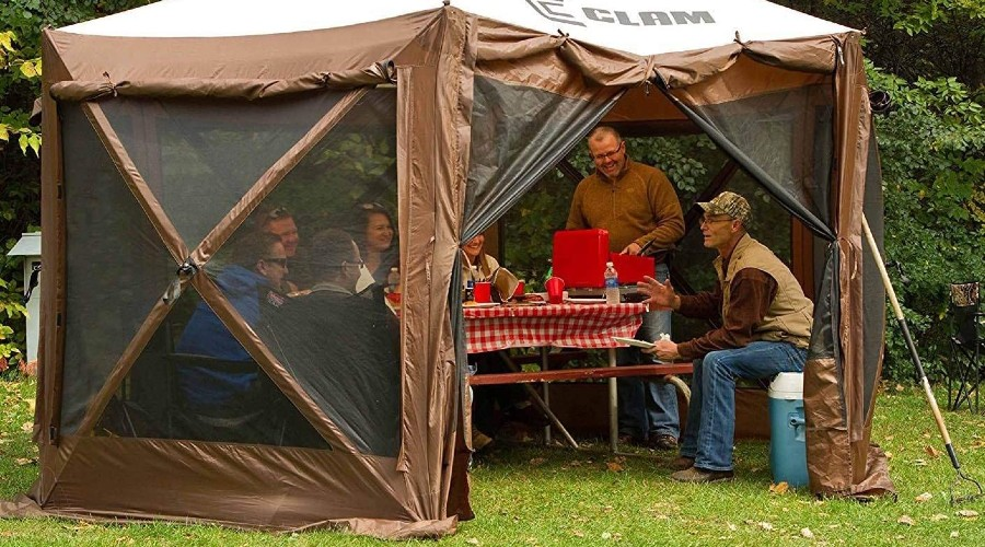 a group of people gathered around a picnic table inside of a backyard tent