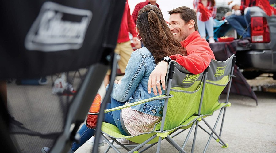 a couple sitting in a two-person camping chair while tailgating