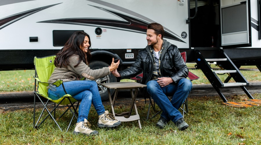 A couple sitting outside a travel trailer in their camping chairs