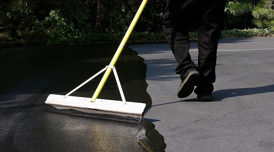 a person applying sealant to an asphalt driveway with a large squeege
