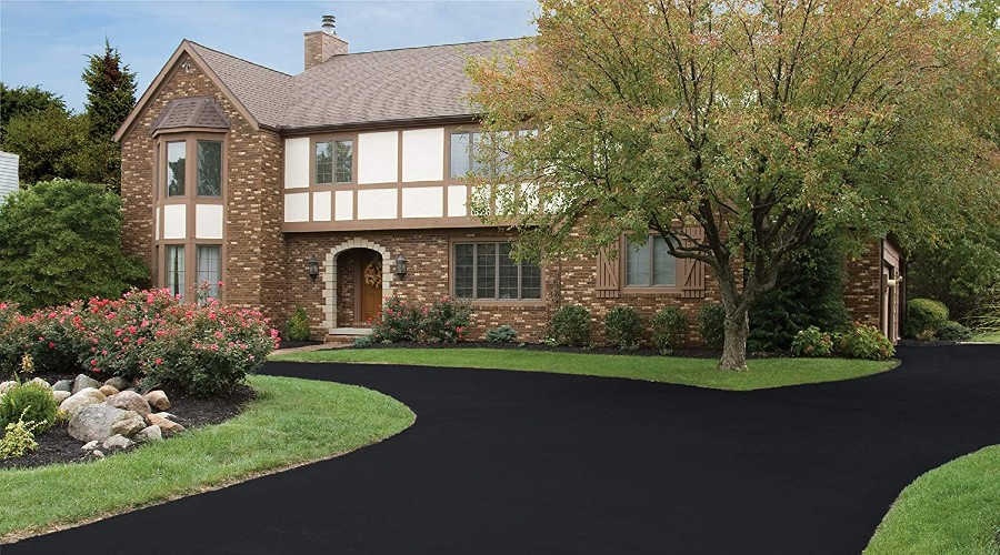 a brick and plaster house with a freshly sealed asphalt driveway